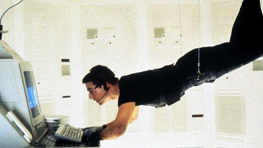 Dans une pièce toute blanche, un homme suspendu par des cables, à l'horizontale, tape sur un ordinateur.