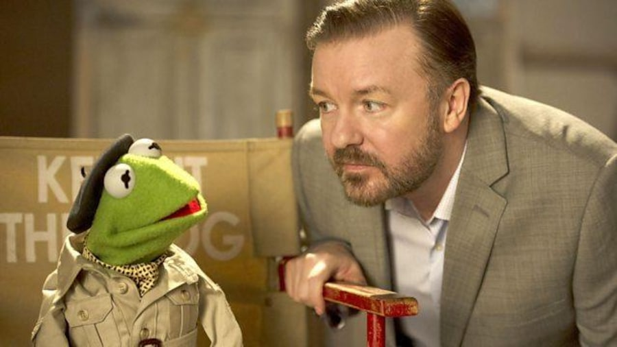 Une marionnette grenouille, assise sur une chaise de réalisateur avec un homme (Ricky Gervais) penché vers elle.