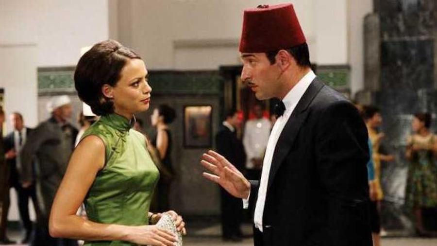 Un homme avec un fès sur la tête parle à une femme en robe verte.