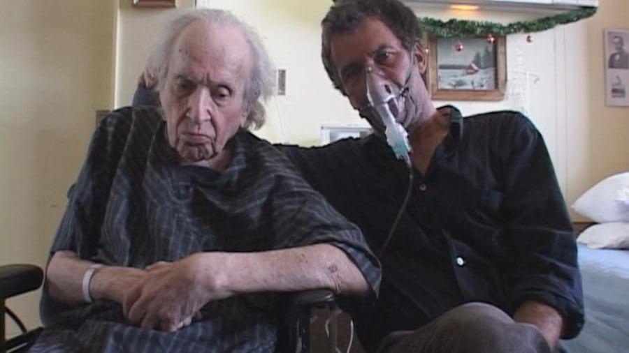 Un homme portant un masque respiratoire (Robert Morin) assis à côté d'un vieil homme en jaquette d'hôpital, sur une chaise roulante.
