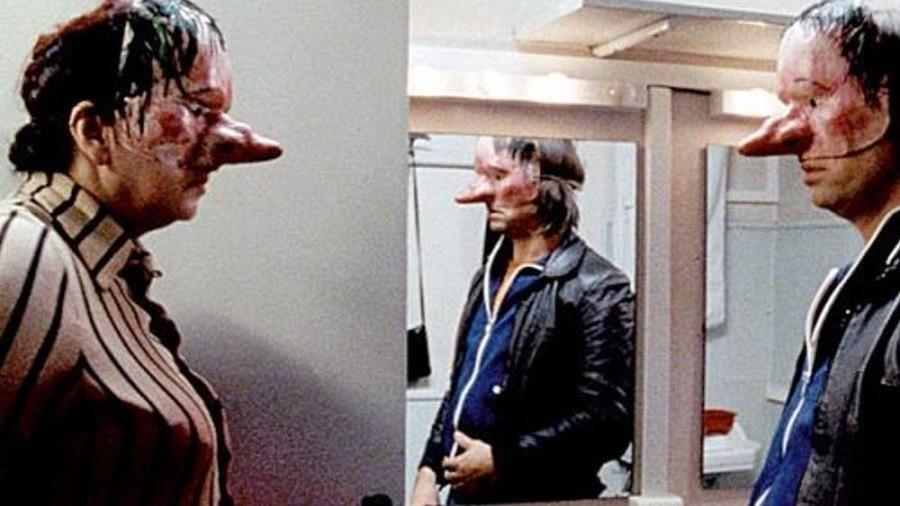 Une femme (Yolande Moreau) et un homme portant des masques se font face.