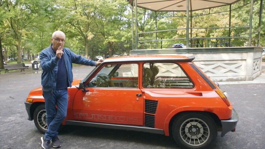 Michel Barrette est installé à côté d'une petite voiture de course dans un parc devant un gazebo.