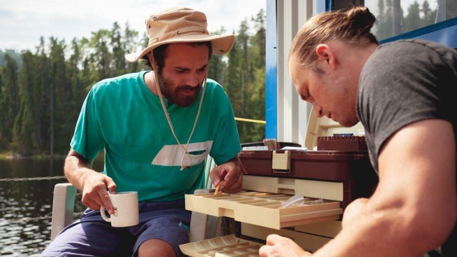 Deux hommes assis (Jean-SImon Leduc et Maxime Dumontier) cherchent quelque chose dans un coffre, sur un bateau.