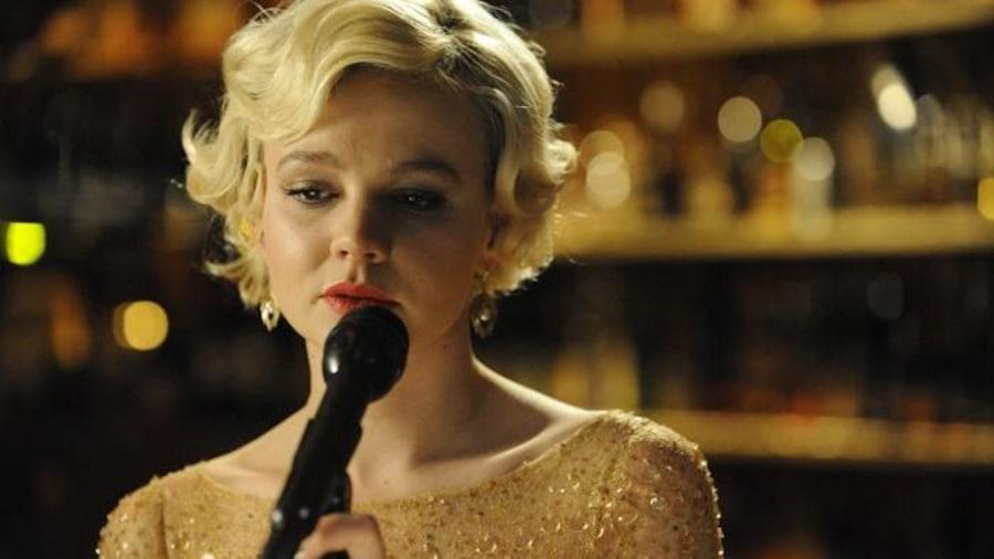 Une jeune femme blonde en robe à paillettes devant un micro.