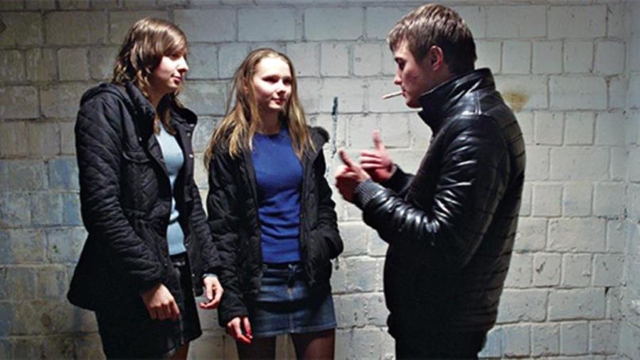 Deux filles et un garçon devant un mur de briques se parlent en langage des signes.