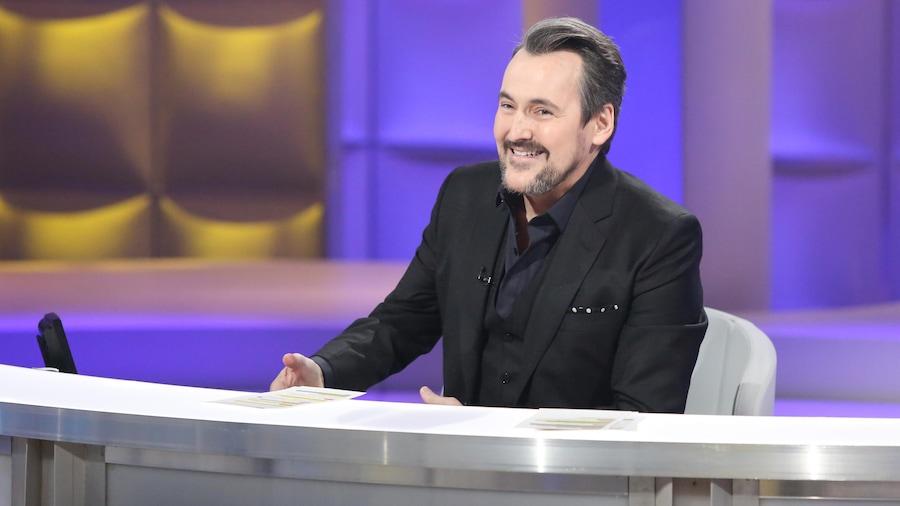 Guy A Lepage est assis sur son siège d'animateur sur le plateau de Tout le monde en parle.