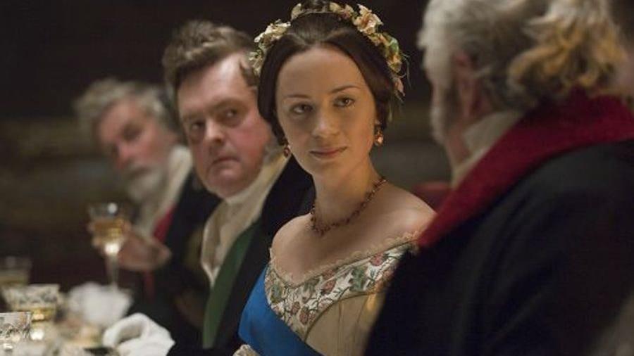 Une femme en robe de bal, une couronne de fleurs sur la tête, assise à table, au milieu d'hommes.