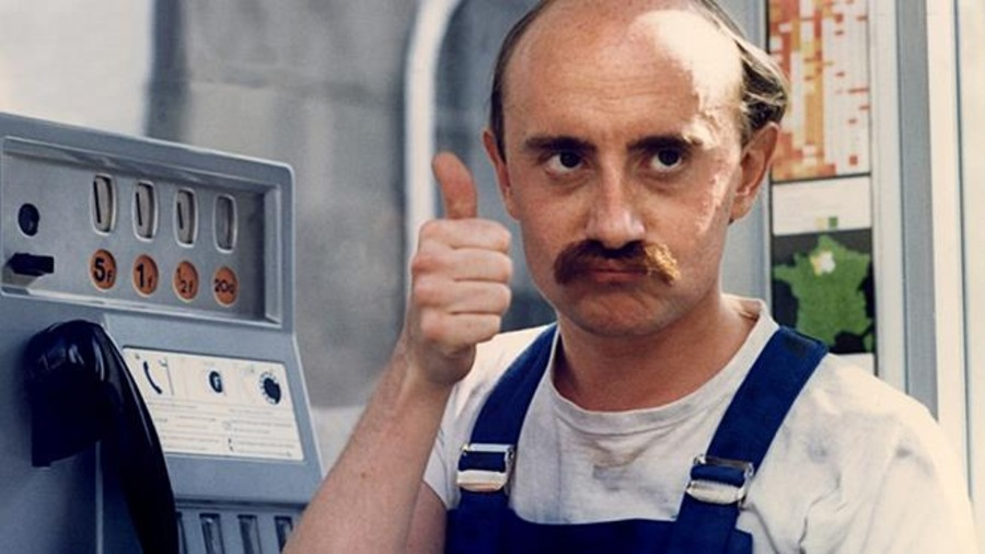 Un homme en salopette bleue, dans une cabine téléphonique, lève le pouce en l'air en faisant une moue.