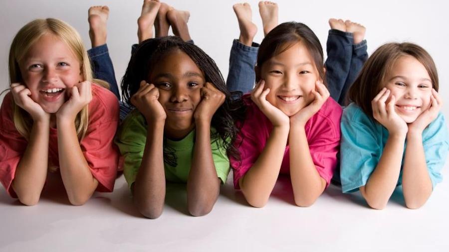 Quatre petites filles allongées par terre.
