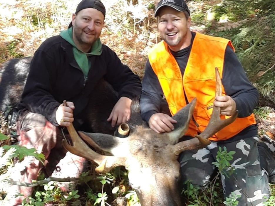 Jonathan Doire et David Dussault tiennent les bois d'un orignal abattu.