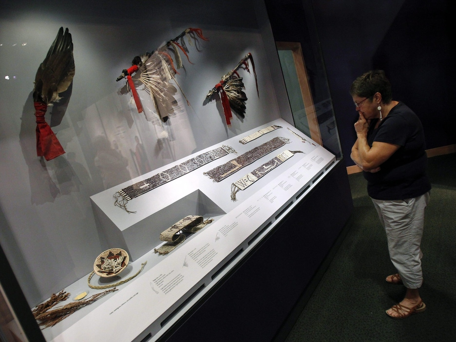 IMAGE DISTRIBUTED FOR THE SMITHSONIAN'S NATIONAL MUSEUM OF THE AMERICAN INDIAN - A visitor views Wampum belts, fans and other diplomatic tools of the Treaty process at the Smithsonian Institution's National Museum of the American Indian's latest exhibition, Nation to Nation: Treaties Between the United States and American Indian Nations, on Tuesday, Sept. 16, 2014 in Washington. The exhibition opens to the public at the National Museum of the American Indian on Sunday, Sept. 21, 2014. (Paul Mor