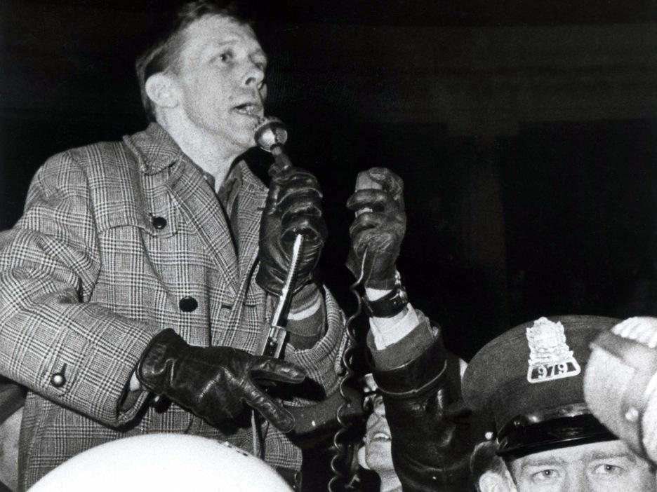 Photo en noir et blanc d'un homme qui parle dans un micro, entourée de policiers et d'une femme.