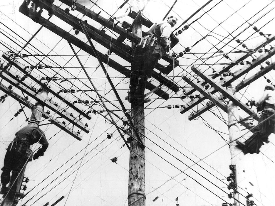 Photo en contre-plongée d'ouvriers juchés dans des poteaux d'électricité