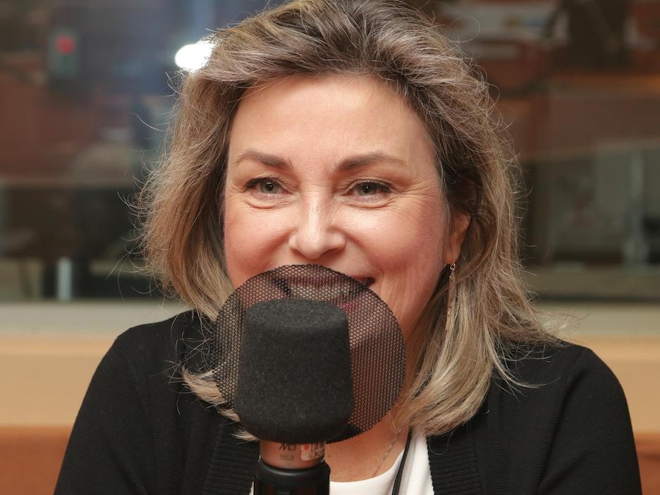 Photo de Monika Ille devant un micro de radio.
