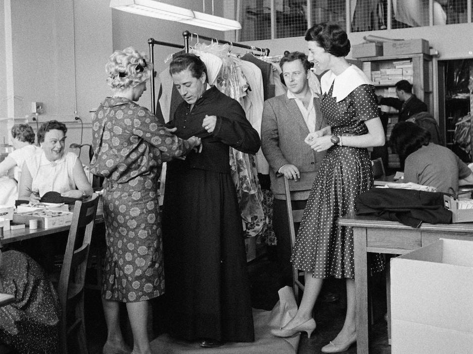 Trois dames et un homme entourent un comédien qui essaie une soutane dans une atelier de couture.