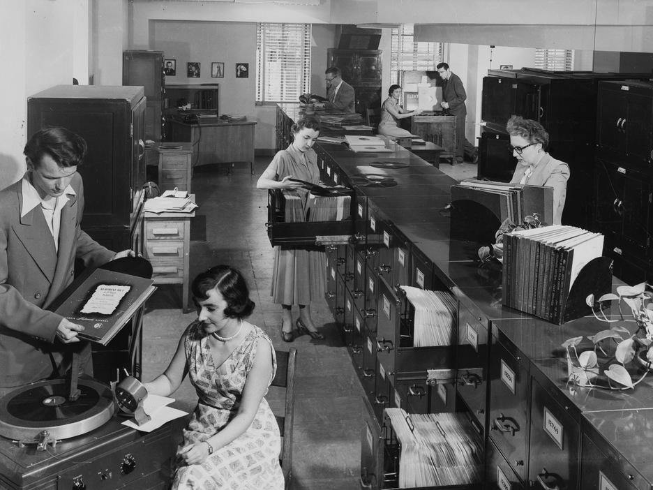 Une dame est dans une grande salle qui contient des classeurs, elle est assise à côté d'un tourne-disque.