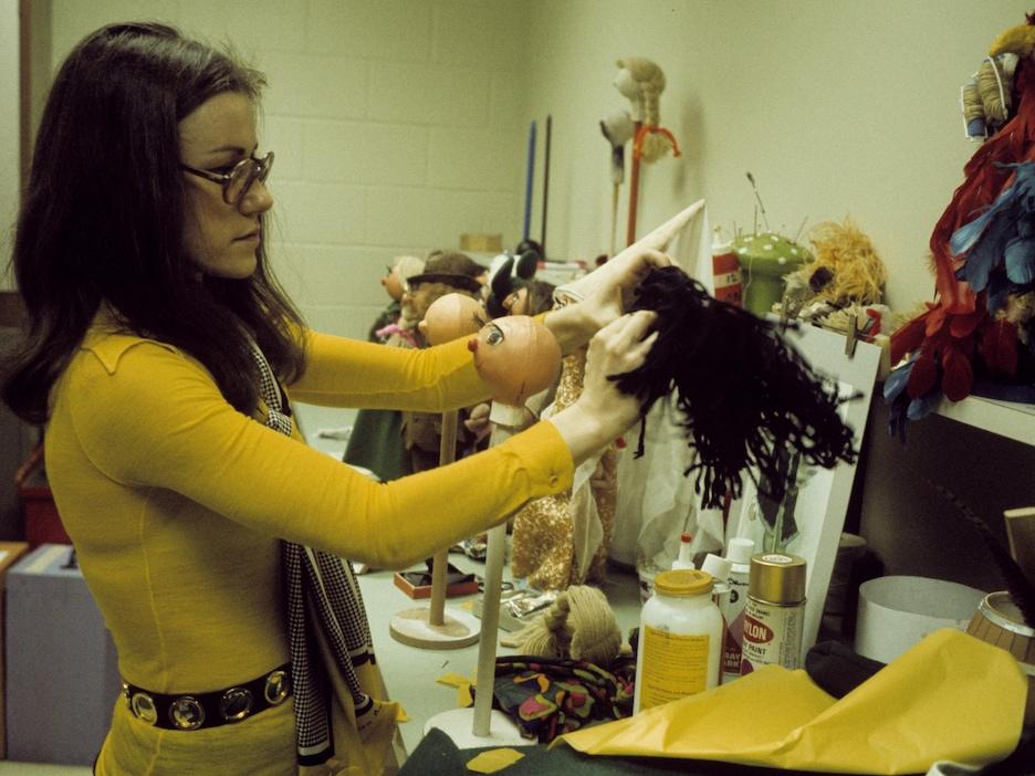 Une dame avec des lunettes s'apprête à poser de petits cheveux sur la tête d'une marionnette chauve.