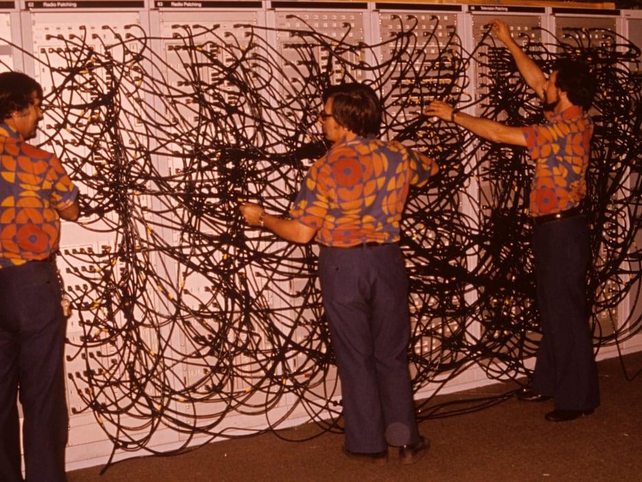 Trois hommes devant un panneau où sont branchés des centaines de fils.