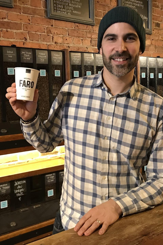 Maxime Fabi sourit à la caméra en tenant un gobelet de café dans ses mains