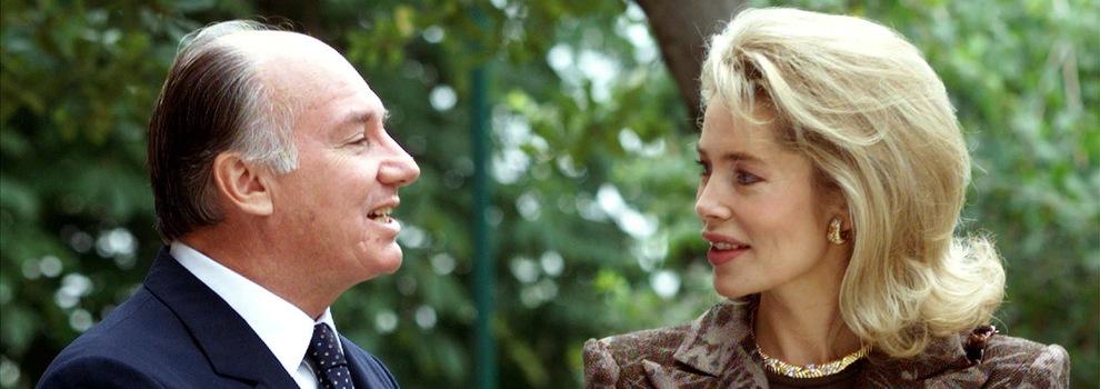 Le prince parle à sa femme, qui l'écoute en souriant. Le couple est entouré d'arbres.