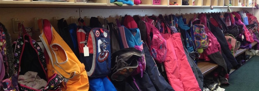 Image de manteaux d'enfants et de sacs d'école sur crochet et sous bacs de rangement.