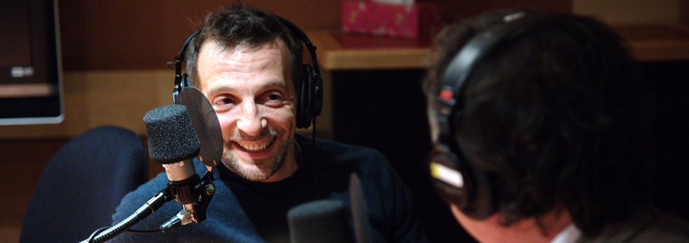 Mathieu Kassovitz sourit en regardant son comparse, de dos sur la photo.